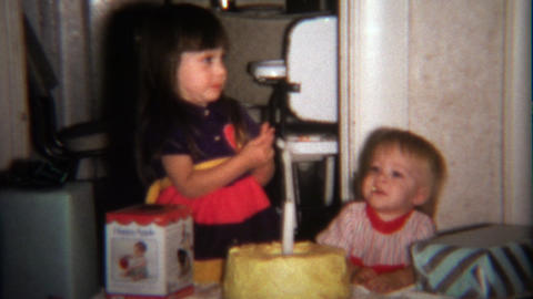 1974: Sister feeding brother birthday cake licking finger Footage