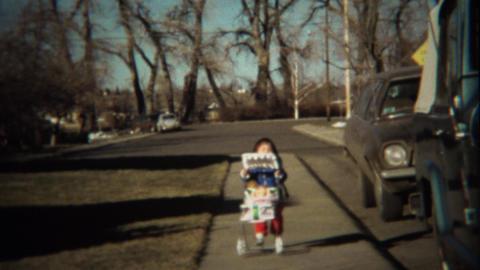 1974: Little girl pushes baby doll in stroller on sidewalk Footage