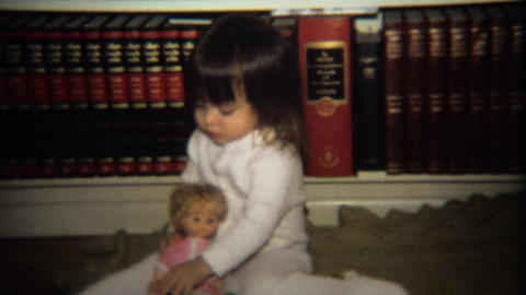 1974: Little Girl Playing With Doll In Front Of Encyclopedia Book Set stock footage