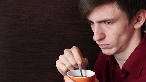 A young guy with an orange mug in his hand stirs a teaspoon looks aside