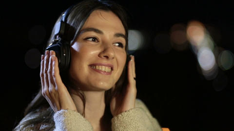 Girl listening to music with headphones at night