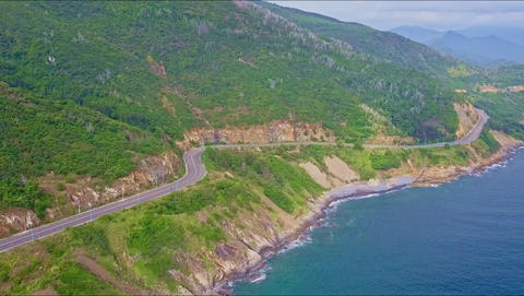 Drone Flies above Highway Running along Green Sea Coast Live Action