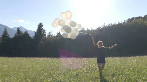 Girl dancing oh the field with bunch of white balloons Footage