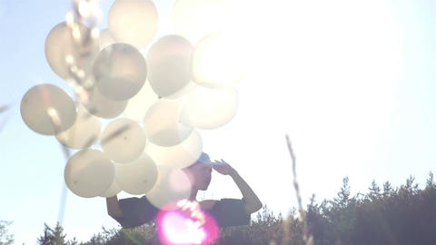 Bunch of white balloons with the girl on the sunny background Footage