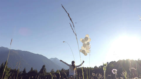 Girl waves to an airplane with white balloons on the wind Footage