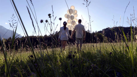 Couple walks with white balloons bunch in green field sunset time Footage