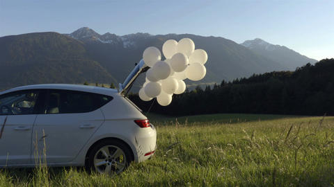 White balloons are flying out of the white car in the mountains Footage