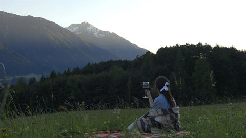 Girl on the picnic with the glass of wine in the alps sunset time Footage