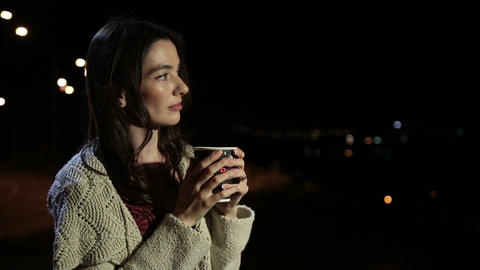 Lovely woman enjoying hot drink in night city Filmmaterial