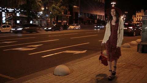 Positive fashionable woman walking on night street
