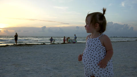 Cute little girl stands on the beach pointing at the sunset, 4K Footage