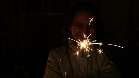 Young girl playing with sparkler happily Footage