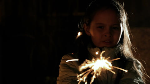 Young girl with sparkler apprehensove then fun Footage