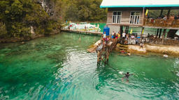 Young boy jumps into the water in the lagoon. Aerial view Footage