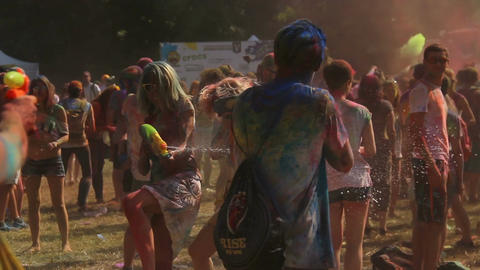 Cheerful youth having water fight using water guns at Holi color festival Live Action