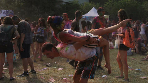 Charming gymnast posing with partner showing interesting tricks at Holi festival Footage