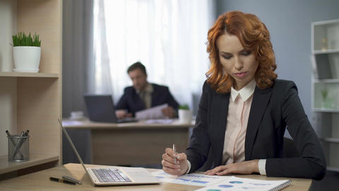 Corporate female employee sitting at desk, checking charts, thinking of results Footage