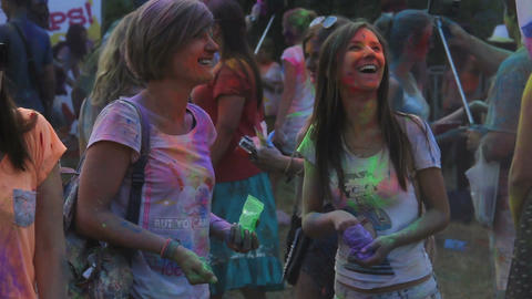 Two female friends spraying colored paint on their friend filming happy moment Live Action