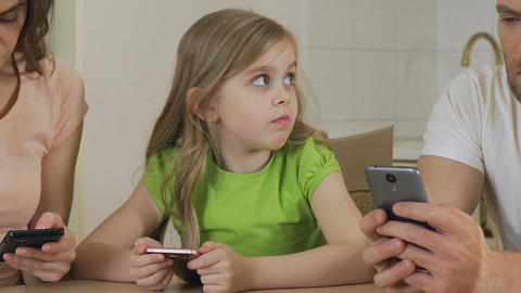 Little girl suffering from lack of parental warmth, mom and dad using phone Footage