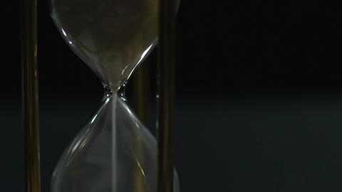 Hourglass with white sand running out, ruthless time flies fast, slow-motion Footage