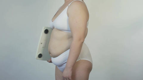 Plus size female holding scales and posing before camera, bodycare and dieting Footage