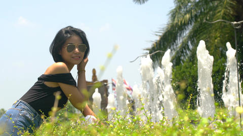 Thai girl wearing sunglasses near fountains in park slow motion Footage
