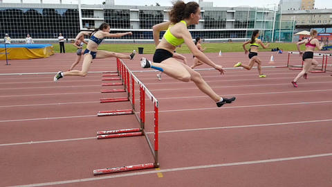 Young women running hurdles track and field. Slow motion Footage