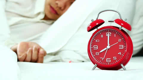 Camera panning Asian women sleep on the bed with alarm clock in the morning on Footage