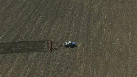 Tractor plowing a field in contry side ビデオ