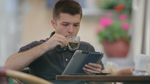 Man using Tablet and Drinking Coffee in Cafe 画像