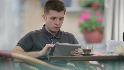 Man using Tablet in Coffee Shop ビデオ