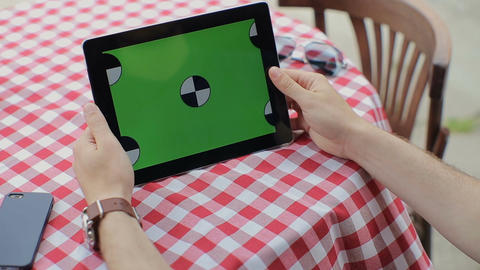 Man using Tablet in Coffee Shop. Tablet with Green Screen 画像