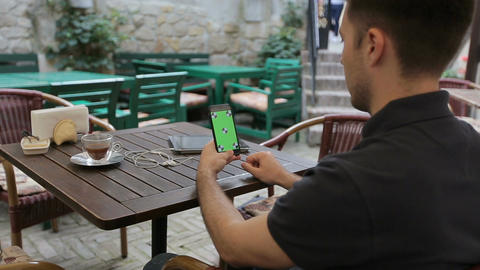 Man using smartphone in Coffee Shop. Smartphone with Green Screen Live Action