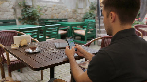 Man using smartphone in Coffee Shop. Smartphone with Green Screen Footage