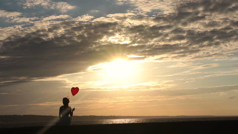 Lonely woman with heart balloon watching sunset Footage