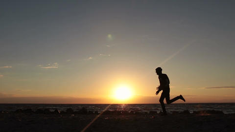 Silhouette of man running at seaside twilight time Footage