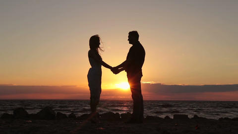 Happy couple holding hands on beach at sunset Footage