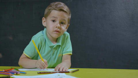 Little boy sitting at table and drawing with colored pencils Filmmaterial