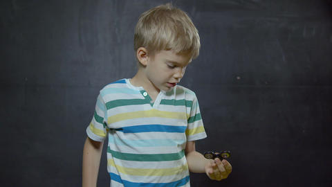 Boy showing skills by flicking spinners with finger ビデオ