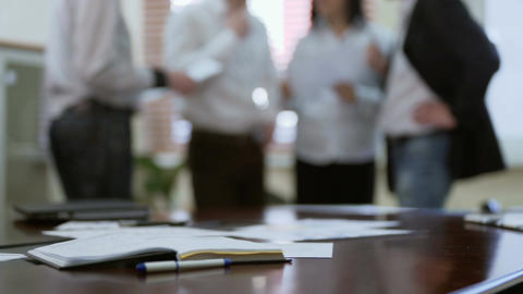 Employee joining colleagues in group discussion over report papers in a meeting Footage