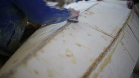 The carpenters polishes a wooden boat at the shipyard Footage