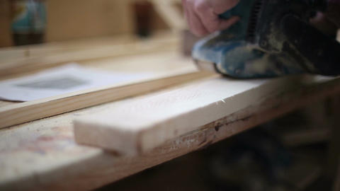 A carpenter polishes a piece of wood Footage
