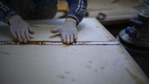 The carpenter seals the joints of the boat at the shipyard Live Action