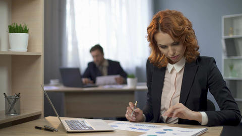 Lady marking statistical diagrams on desk, contemplating results, annual report Footage