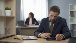 Company worker typing on laptop, searching information on tablet, analysis Footage