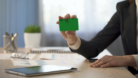 Businesswoman showing business card with green field, banking services ad Footage