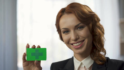Smiling young woman holding green colored card in hand, new convenient service Footage
