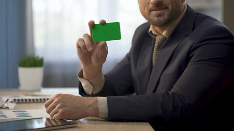 Employee sitting at office desk, showing card in green color, insurance plan ビデオ