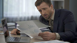 Man surrounded by paperwork at office looking at graphs, head falling on folders Footage