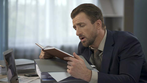 Exhausted businessman looking at long list in notebook and putting it on head Footage